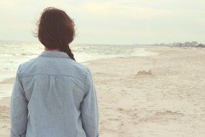 אישה מהורהרת מביטה אל הים
